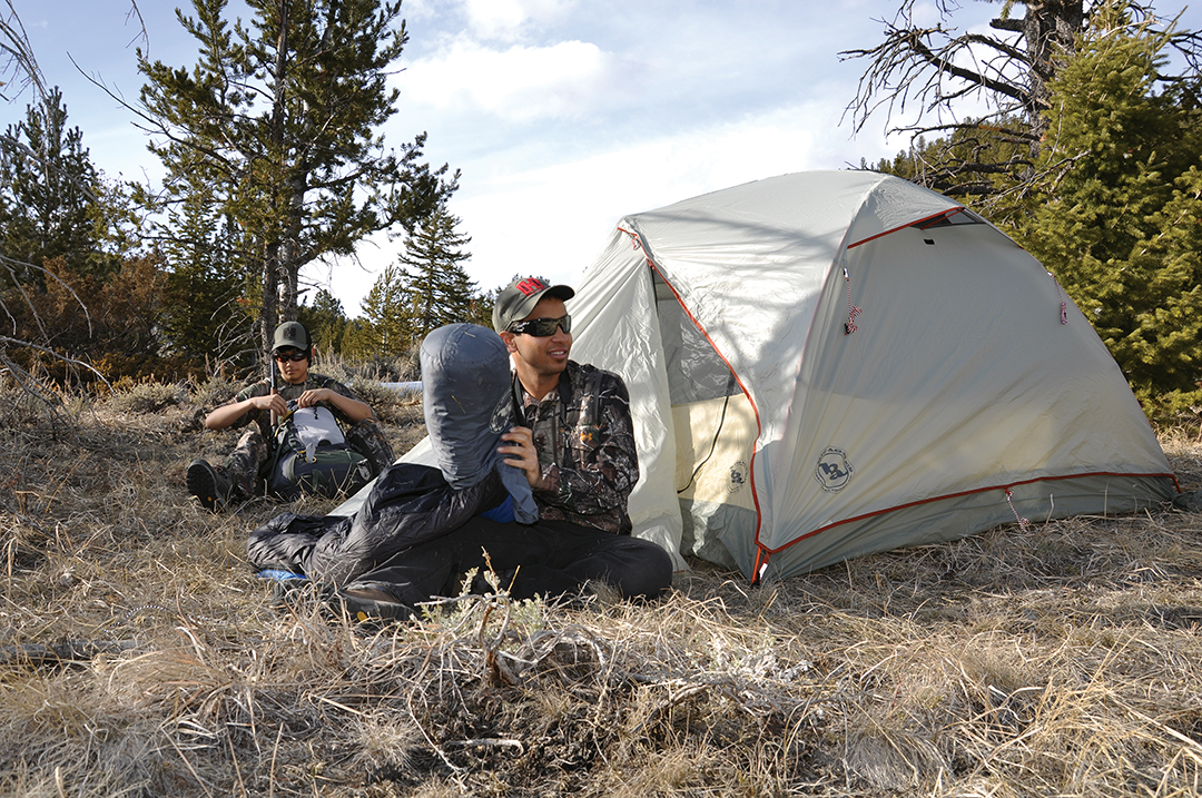 A tent large enough to house one person more than the actual number of people in the group does not require much extra weight and is worth it for the extra room. These two hunters are sharing a three-person tent.