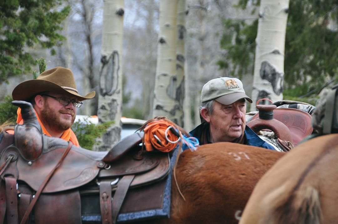 These hunters are checking the rigging on a saddled mount. Pay attention to the rigging on your horse so problems can be identified if they arise.
