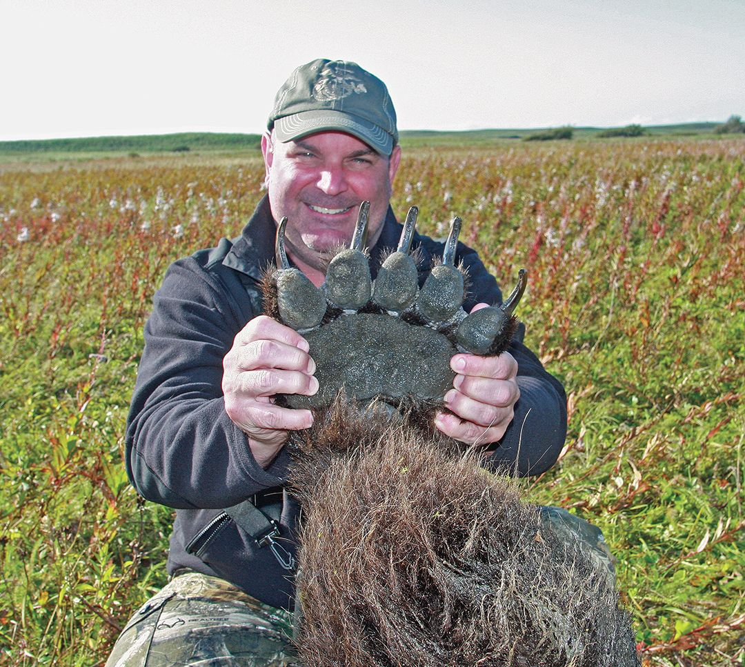 Jeff holds up the massive paw of his brown bear.
