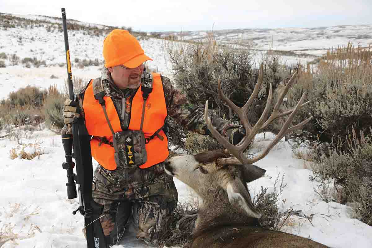 Brad admires the mature buck he shot during a Colorado migration hunt.