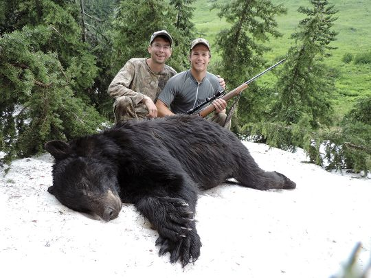 Nate Corley and Joel pose with their bear after a rather exciting day on a wilderness mountainside.