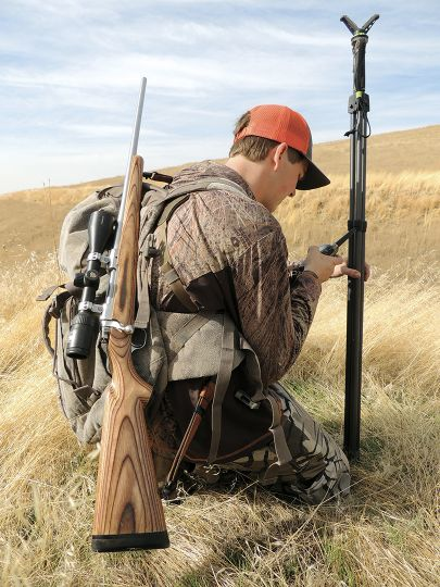 Taking a break in the middle of a long hunt, Tanner Roberts checks his location on a ridgetop.