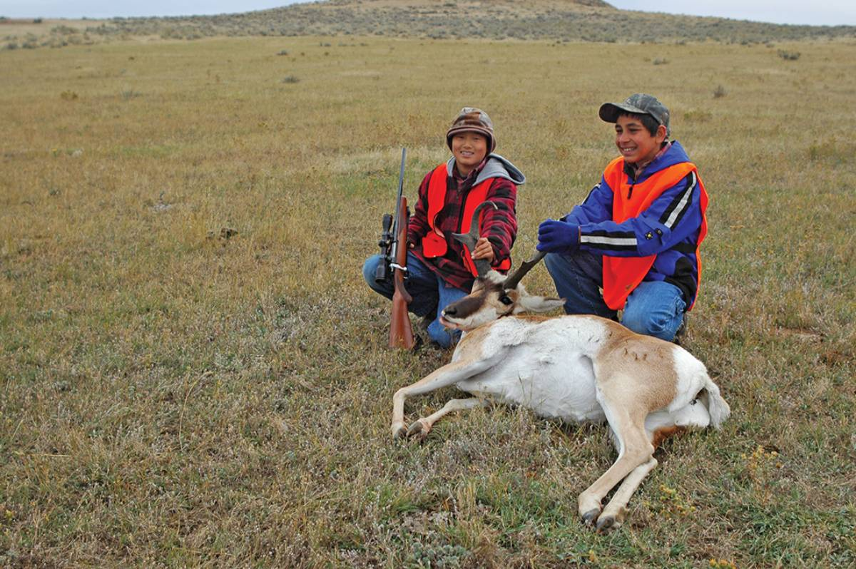 Jack's sons smile for a photo with his eldest's first pronghorn, the result of an impromptu interception.