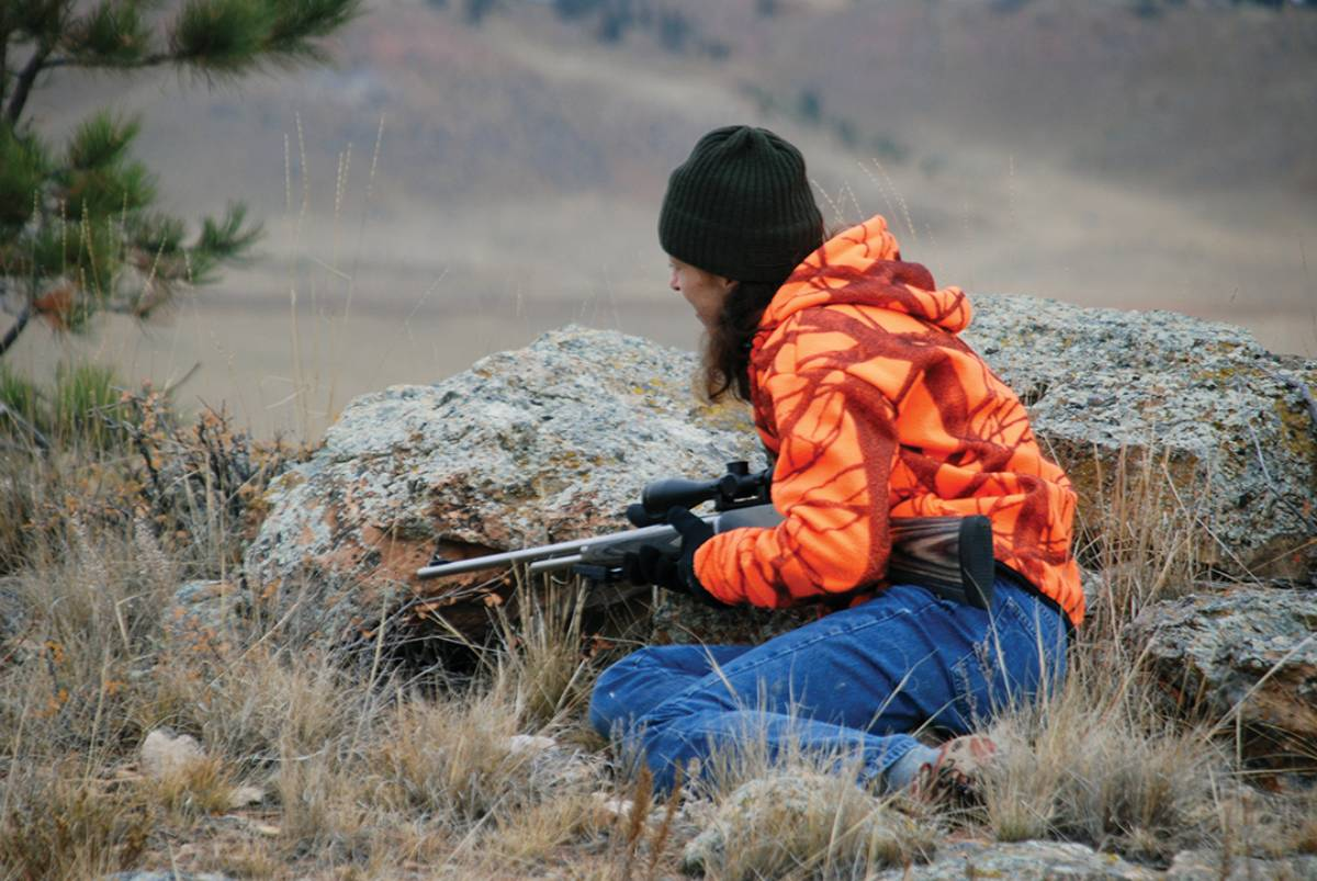 A large rock gives Lisa Ballard a good hideout while waiting to ambush pronghorn in eastern Montana.