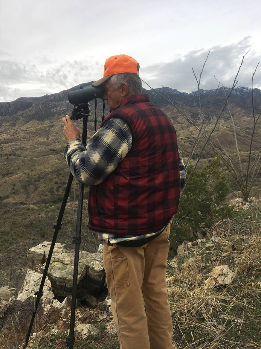 Duwane Adams stands behind his tripod-mounted binocular glassing for trophy deer in southern Arizona. He frequently finds bucks more than a mile away.