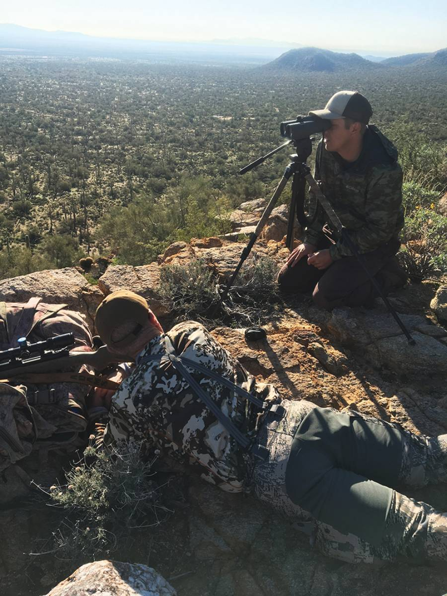 Tol is preparing to shoot from prone while guide Shane Yount gives him landmarks to find the buck in the scope.